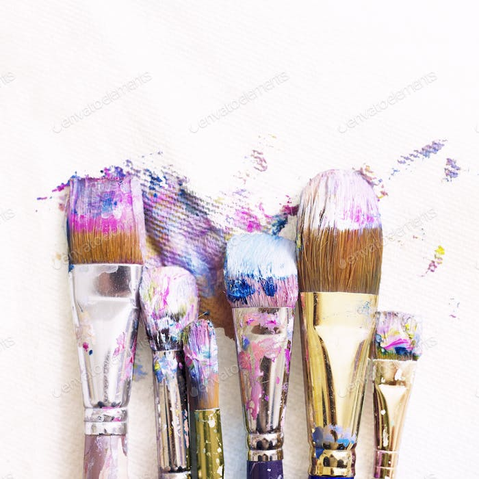 Six colorful paintbrushes lined up on a white slightly textured paper towel background.