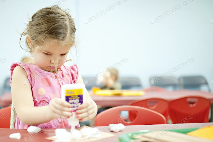 girl pouring glue all over a craft