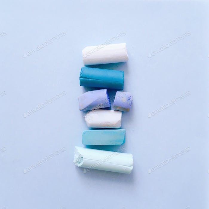 Reihe von hellblauen Pastellkreiden auf einem soliden hellblauen Hintergrund aufgereiht.