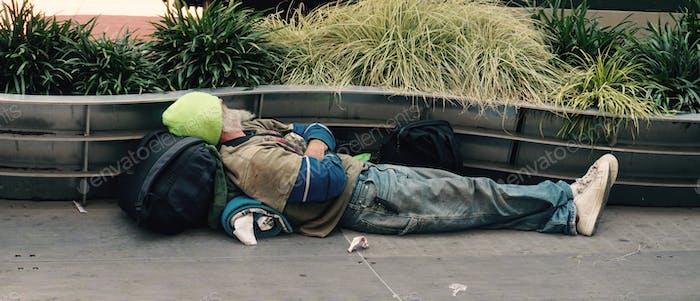 Obdachloser ruht auf dem Bürgersteig