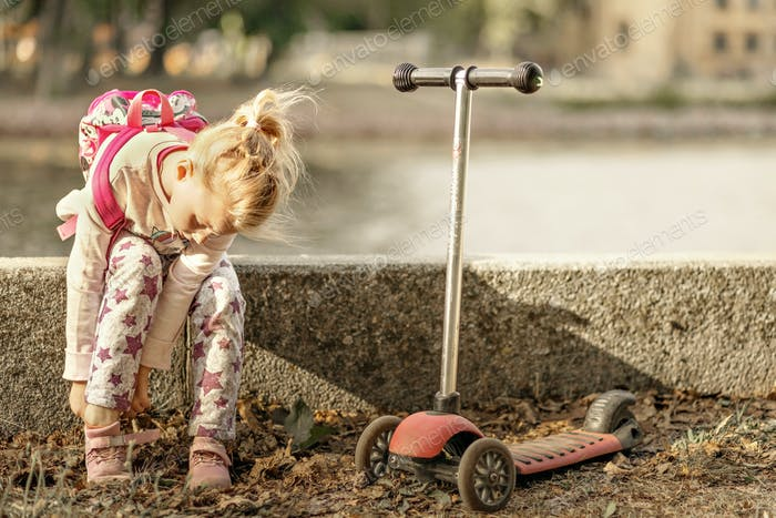 A little girl toddler is sitting in the park, putting on sneakers for riding a scooter