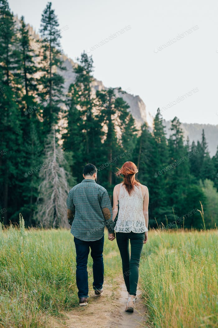 Young cute couple holding hands while walking away  on a dirt trail.