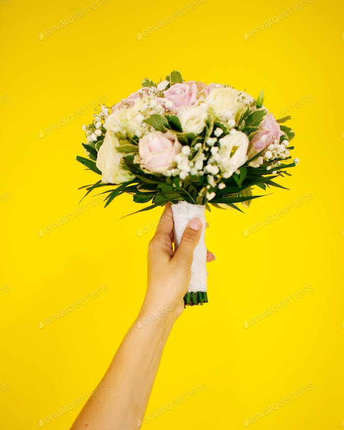 Hand holding a Bouquet of flowers on a yellow background wall