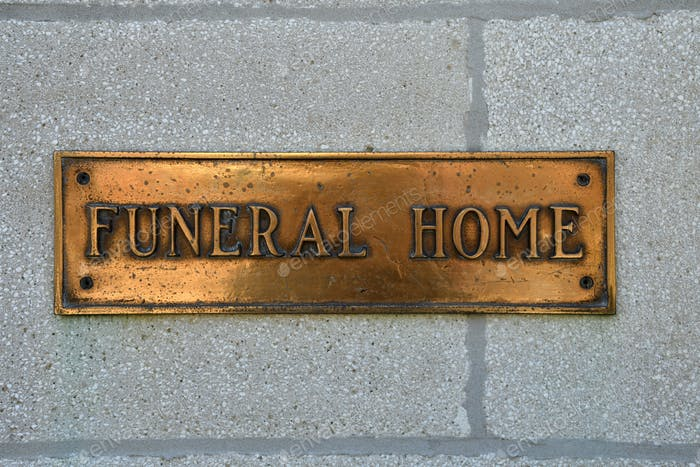 A brass Funeral Home sign on a wall. Morticians, funeral directors