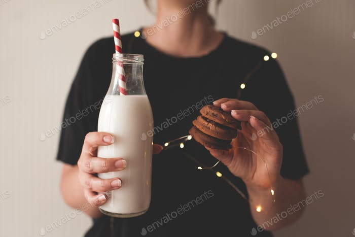 Woman holding tasty homemade cookies and bottle of fresh milk over glowing lights close up.