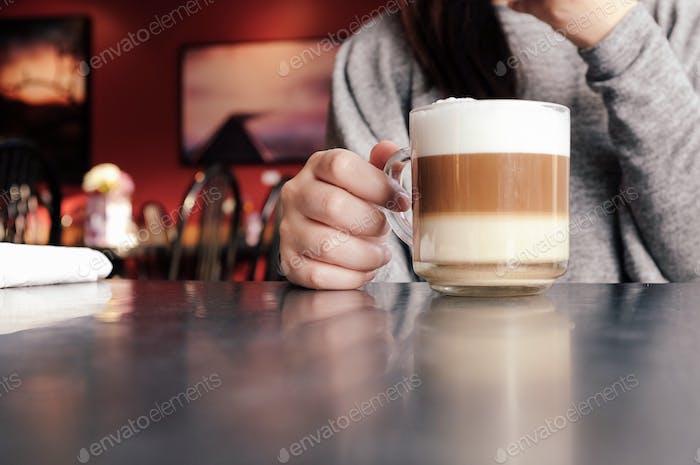 Mädchen/Frau hält Tasse Kaffee