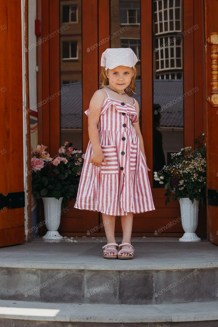 A little beautiful girl in a striped sundress