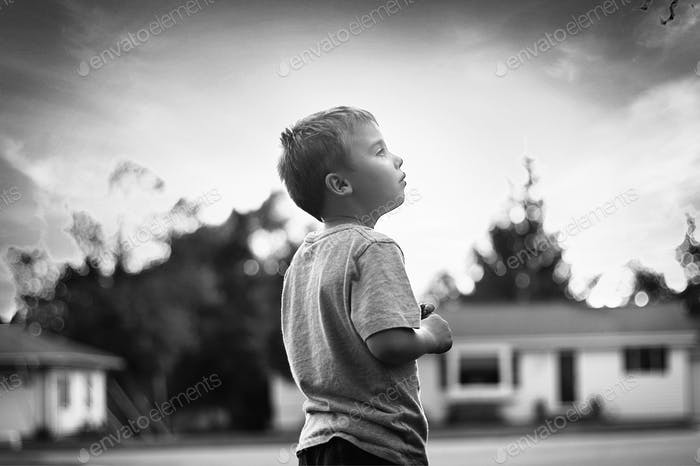 Little boy looking at storm clouds