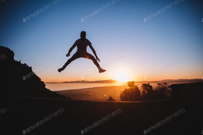 Silhouette of young men jumping in epic sunset with scenic landscape