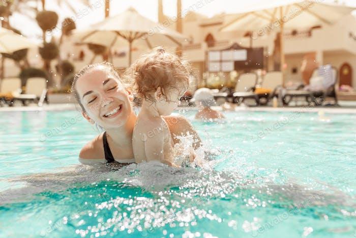 Mãe e filha brincando na piscina nas férias em família no país tropical. Fam