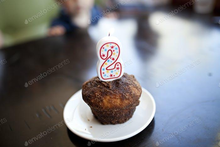 Vela em um muffin de aniversário