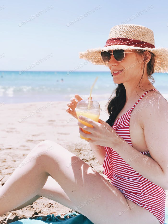 Smiling girl in the straw hat is drinking juice on the beach