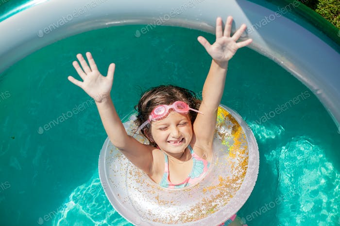 A girl in the pool with a swim ring