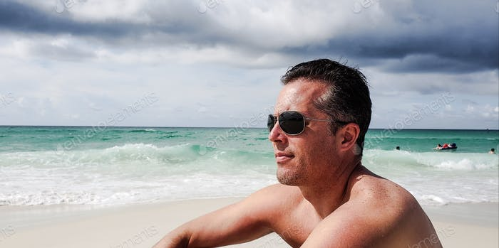 Millenial man in sunglasses is sitting on sand  at the beach thinking that his last day of vacation