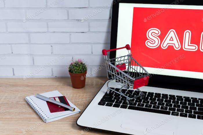 Concepto de comercio electrónico. Portátil con inscripción roja hormiga carro de juguete sobre mesa de madera
