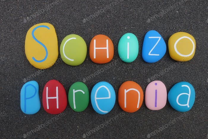 Schizophrenia word composed with multi colored letters over black sand