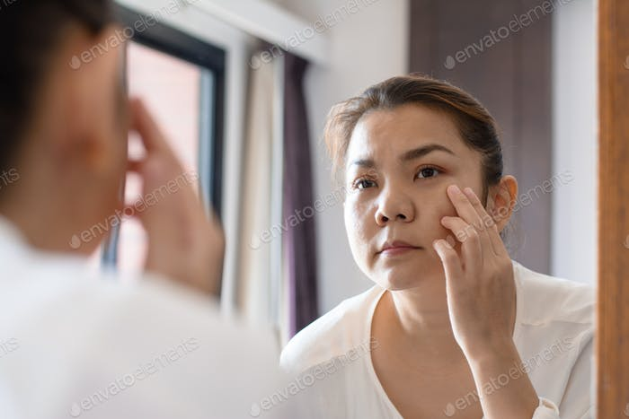 Middle aged asian woman looking at wrinkles in mirror