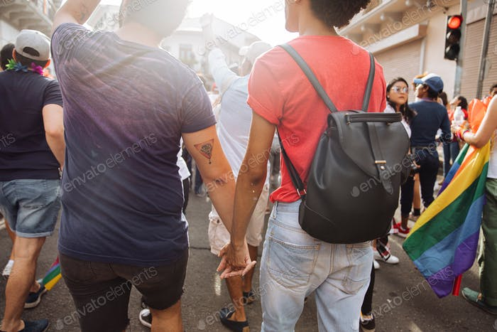 A couple of gay men holding hands in the lgbtq+ pride parade in latin america (Panama)