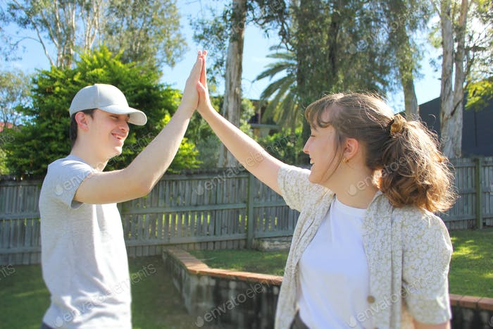Generation Z teenager siblings high five each other