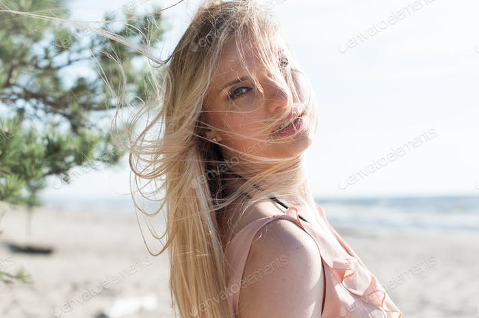 Millenial woman with hair fluttering in the wind at the beach in summer
