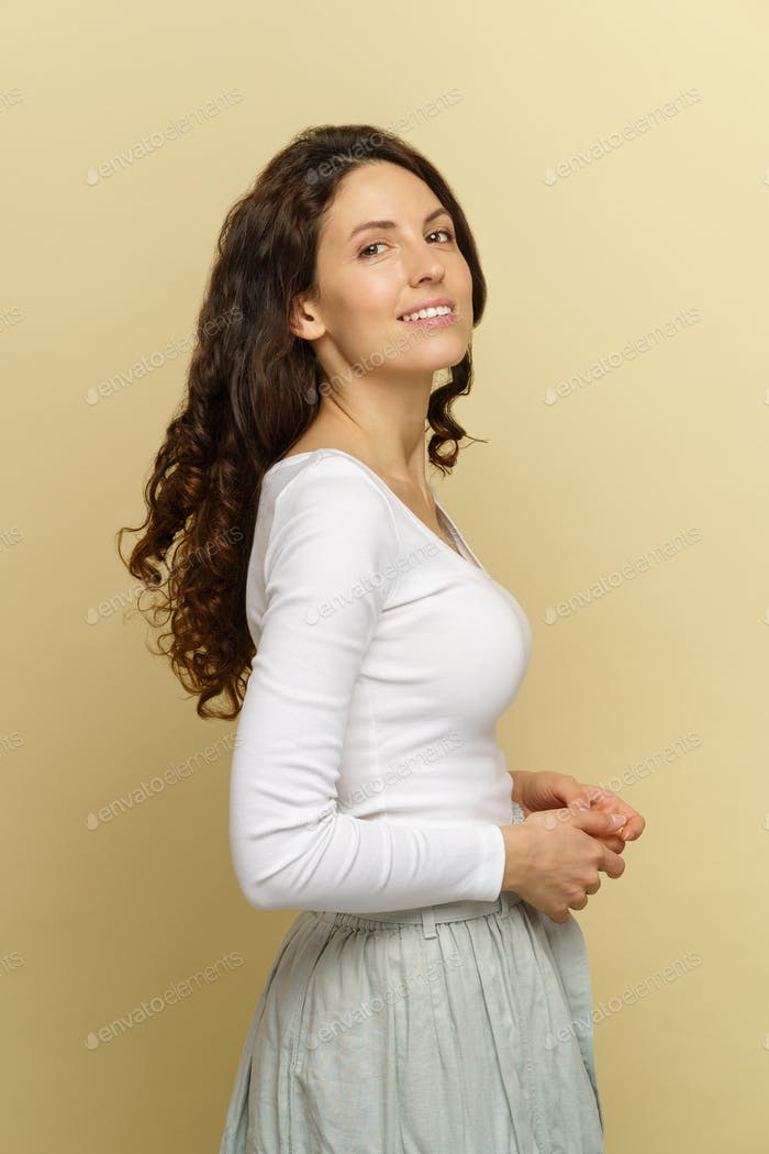 Studio portrait of smiling brunette woman with curly hair looks at camera expressing happiness.