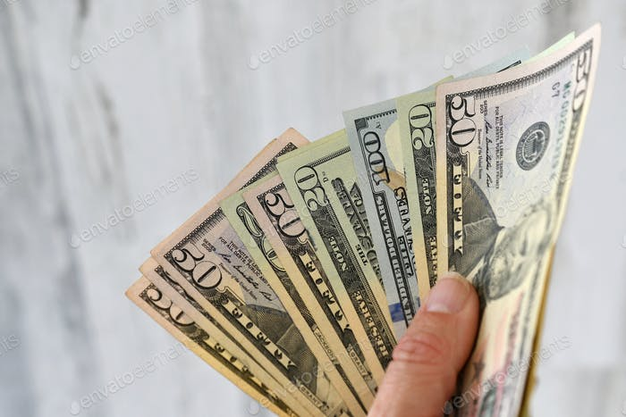 A female holds a handful of money, currency, cash, salary, extra income, side hustle, earnings