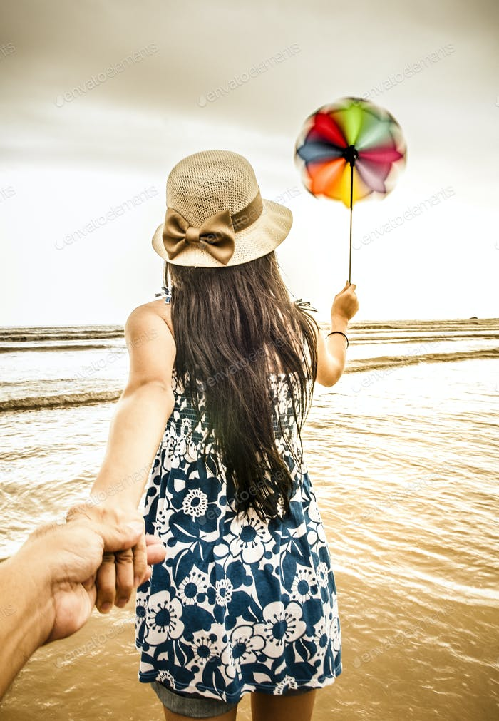Rear view of following young female adult holding hands and wind propeller toy on the beach
