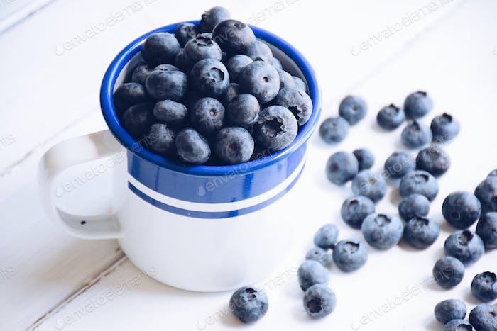 Blueberries in an enamel cup
