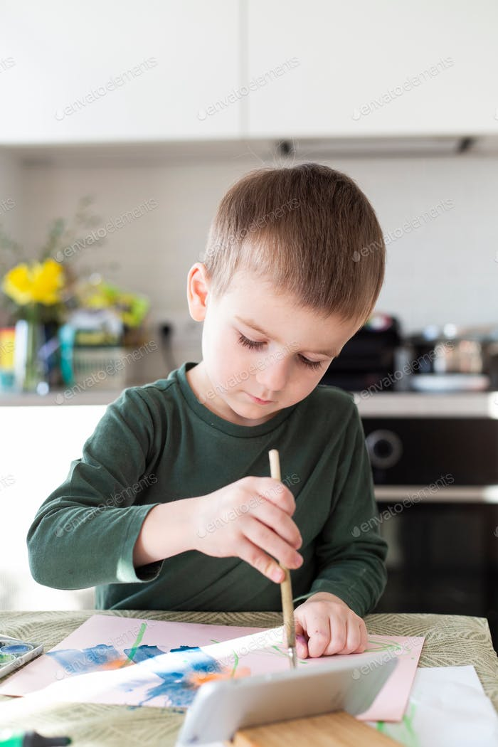 boy of European appearance paints in the kitchen