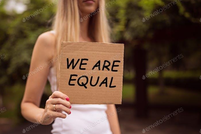 Mujer tomada de la mano signo de igualdad de género con la inscripción «somos iguales»