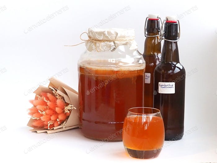 Kombucha, a healthy homemade carbonated drink, jar, bottle and glass of kombucha