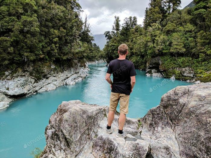 Man looking at emerald lake