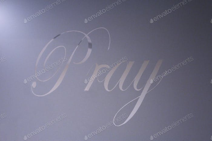 The word PRAY is etched in a glass door.