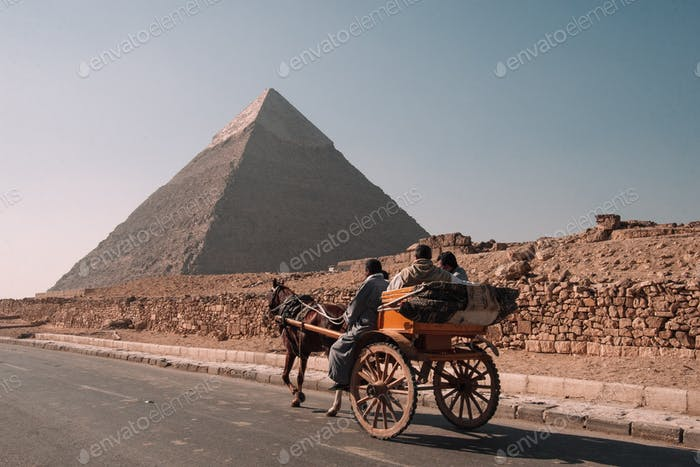 A horse drawn carriage with tourists passing by the pyramids of Giza.