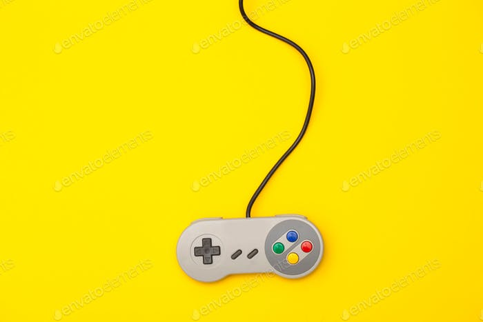 Retro computer gaming controller on a yellow background