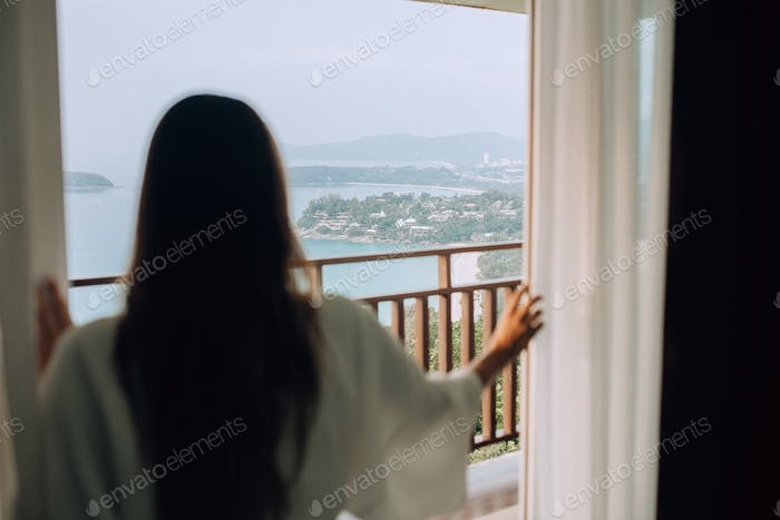 Girl looking on the morning view from her window