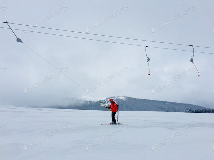 Single skier on the teleski with view of mountains in the background
