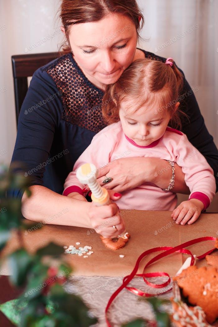 Mama mit ihrer kleinen Tochter dekoriert gebackene hausgemachte Lebkuchen Weihnachtsplätzchen mit Zuckerguss