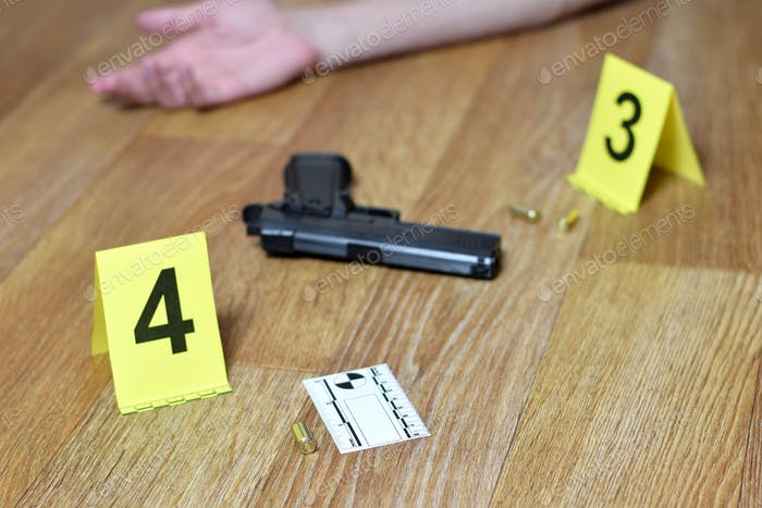 Hand of young man and gun with gunshells on wooden floor