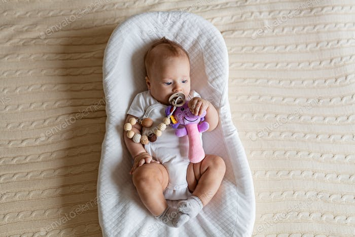 Cute blonde baby three months old lying in cocoon at home. Kid holds stuffed sound toy, sucks nipple