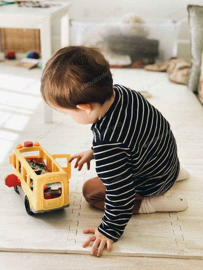 Kleiner Junge spielt mit seinen Spielzeugen, während er im Boden sitzt. #debb\_a /Kindheit
