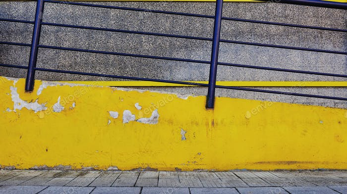 Yellow architectural minimalism. Yellow concrete access ramp and blue metal fence.