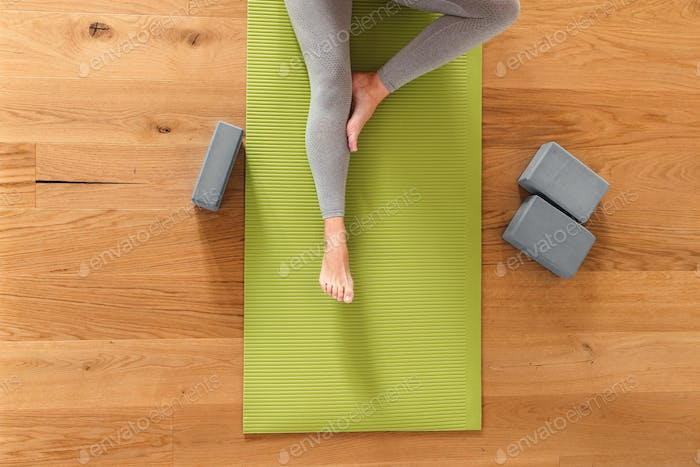 Overhead view of a young woman working out from home, doing yoga and stretching on a mat