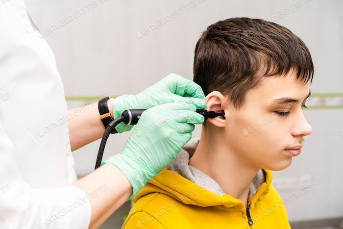 Preventive inspection of a teenage boy in a medical facility. Otorhinolaryngologist doctor
