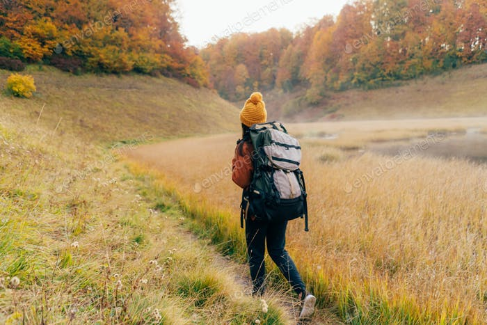 A woman with a large hiking backpack goes on an expedition along the trail through the autumn beauti