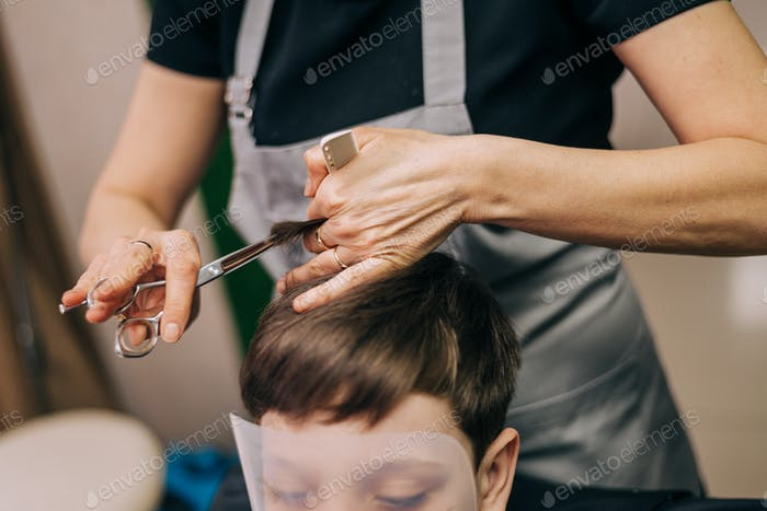 Little kid boy in the barbershop or hairdressing saloon. Barber is doing haircut for a toddler