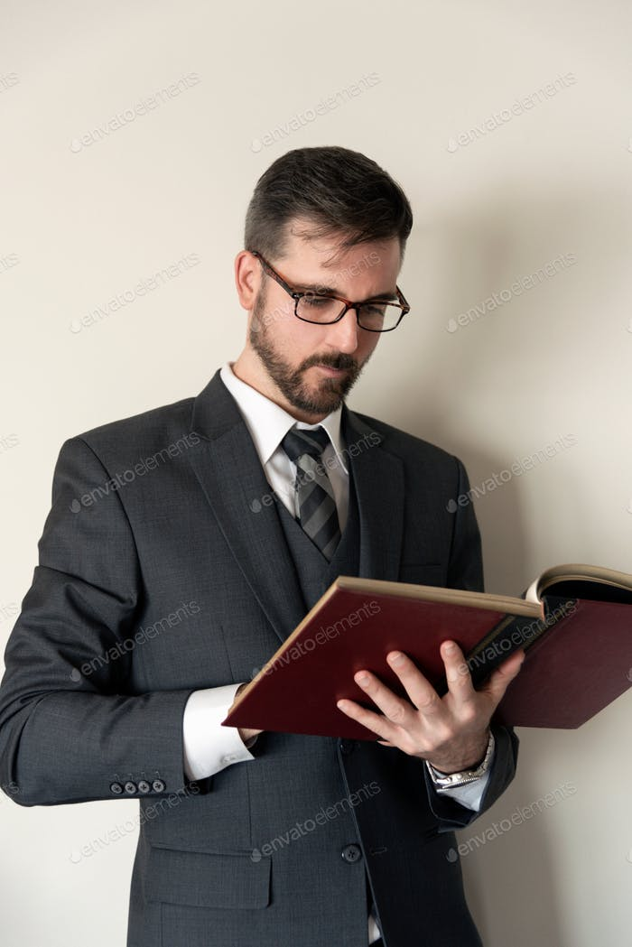 Man in suit reading a from a large hardcover book