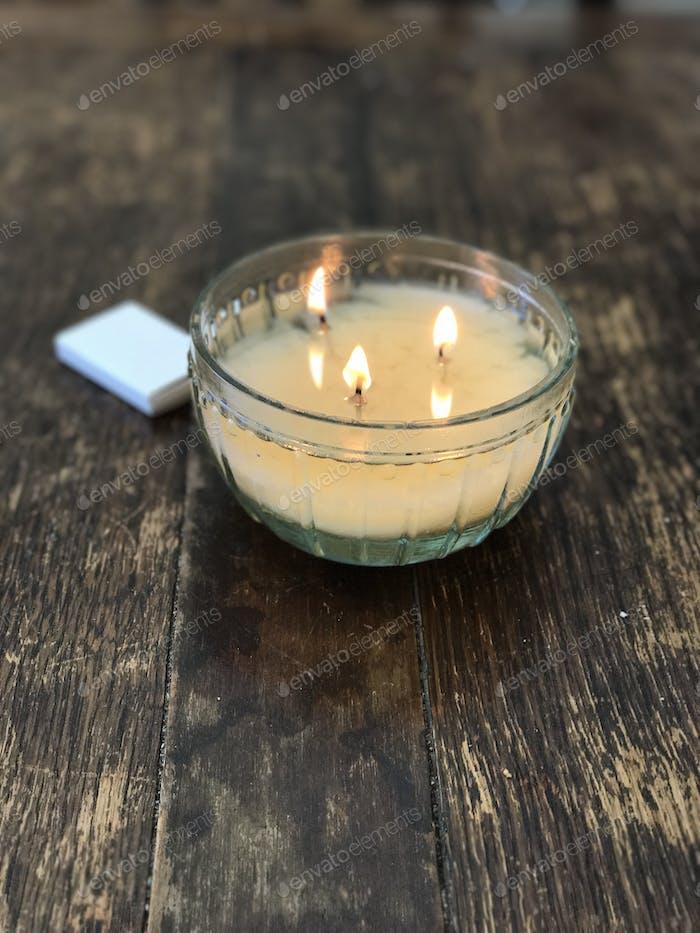 Kerze mit drei Dochten in einem alten Holztisch