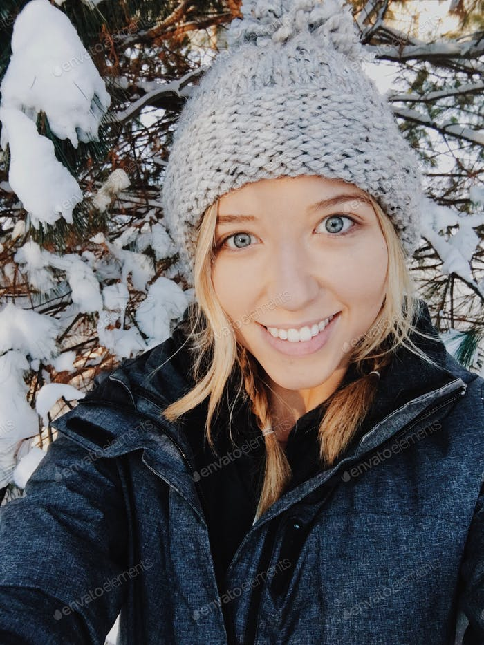 Girl wearing a knitted beanie in the snow