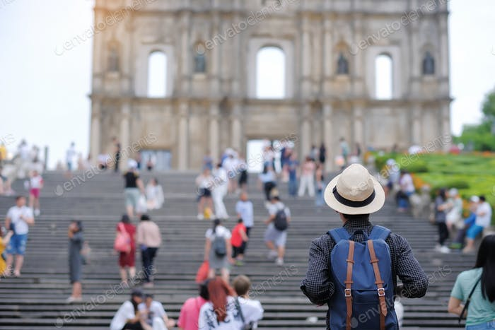 Young man traveling backpacker with hat, Asian hipster traveler looking to Ruins of St